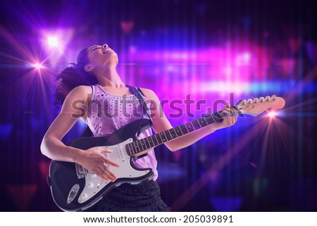 Pretty girl playing guitar against digitally generated cool nightlife design - stock photo