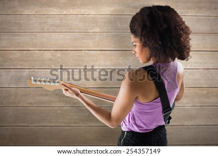 Pretty girl playing guitar against wooden surface with planks - stock photo