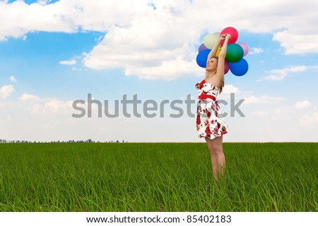 pretty girl playing with balloons in a field on holiday - stock photo