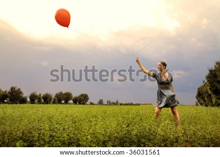 pretty girl playing with red balloon - stock photo