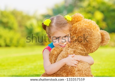 Pretty girl playing with soft toy outdoor, cute infant having fun on backyard in spring time, happy childhood concept - stock photo