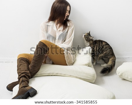 Pretty girl portrait sitting on cushions and looking at cat - stock photo