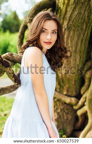 Pretty girl pose to camera at park with sunlight background