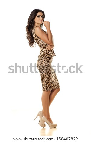pretty girl posing in a leopard print dress on white background - stock photo