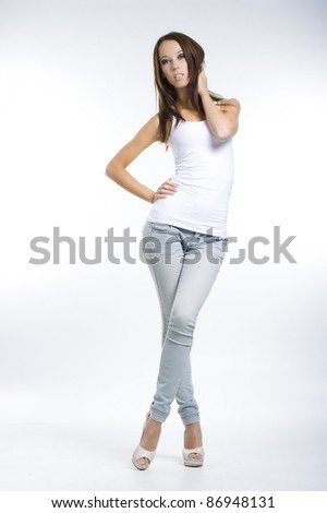 Pretty girl posing in jeans and a white top