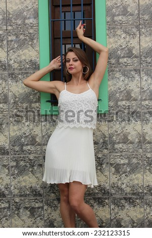 Pretty girl posing on a rustic wooden window - stock photo