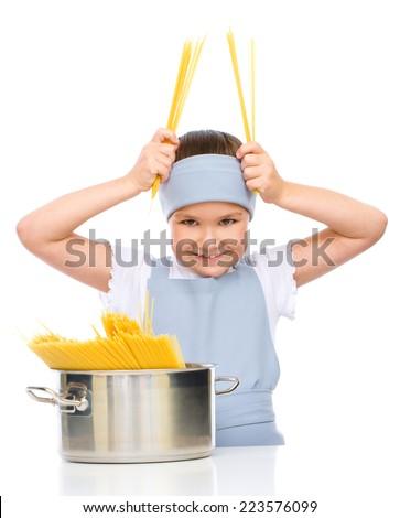 Pretty girl preparing spaghetti, isolated over white - stock photo