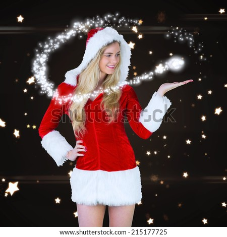 Pretty girl presenting in santa outfit against bright star pattern on black - stock photo