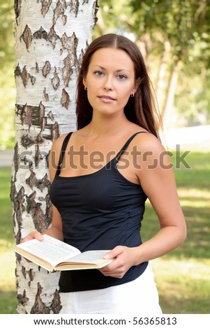 Pretty girl reading a book in a city park - stock photo