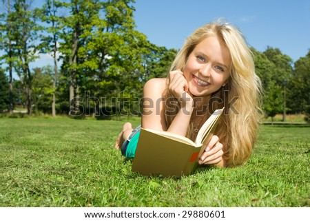 Pretty girl reading a book on grass
