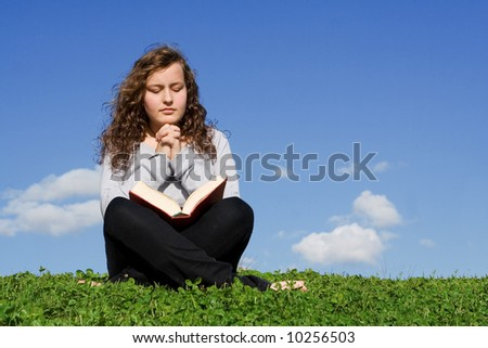 pretty girl reading bible and praying - stock photo