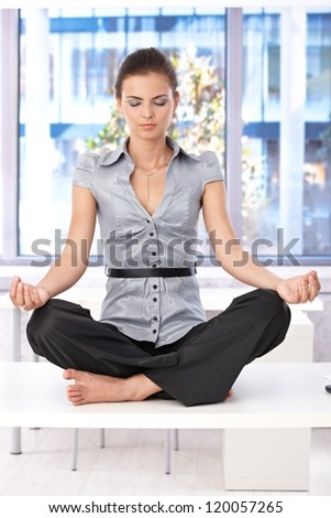 Pretty girl relaxing on top of desk in office, eyes closed. - stock photo