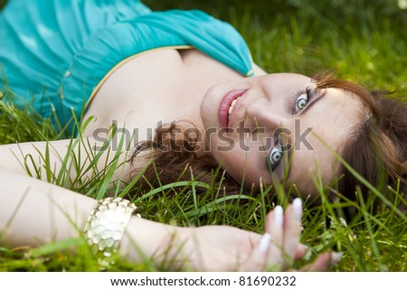 Pretty girl relaxing outdoor in green grass - stock photo