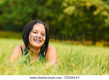 Pretty girl relaxing outdoor on green grass