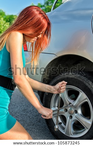 Pretty girl removing a wheel on a road - stock photo