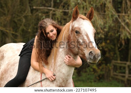 Pretty girl riding a horse without any equipment in autumn - stock photo