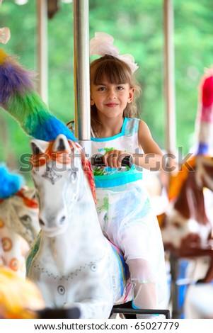 pretty girl riding a merry go round - stock photo
