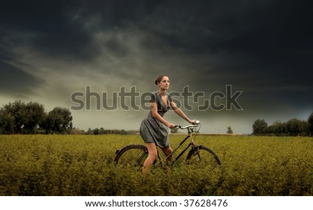 pretty girl riding bike in the countryside - stock photo