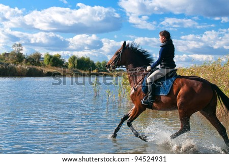 Pretty girl riding horse in shallow river water - stock photo