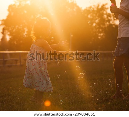 Pretty girl runs for the bubbles in the park on the sunset - stock photo