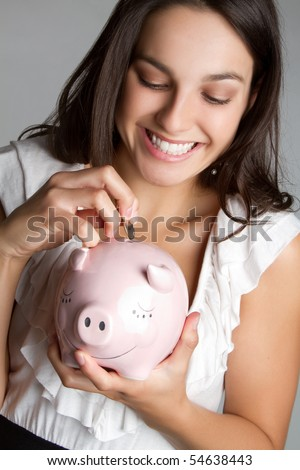 Pretty girl saving money in piggy bank - stock photo