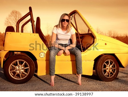pretty girl seated on a small car - stock photo