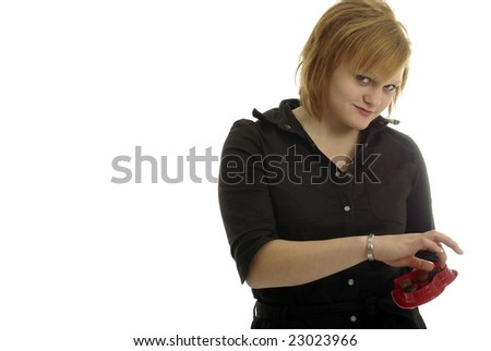 Pretty girl selects chocolate from heart shaped box - stock photo