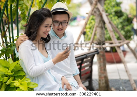 Pretty girl showing photo on smartphone to her boyfriend - stock photo