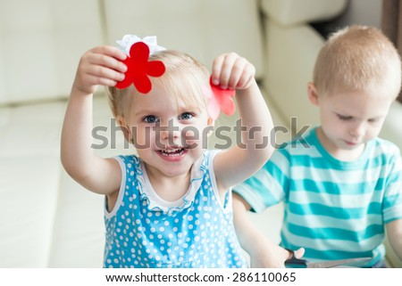 pretty girl shows a cardboard cut out of red flowers sitting next to her brother, and that is cut with scissors - stock photo