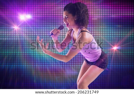 Pretty girl singing against digitally generated cool disco background - stock photo