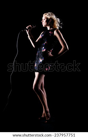 pretty girl singing at the party. on black - stock photo