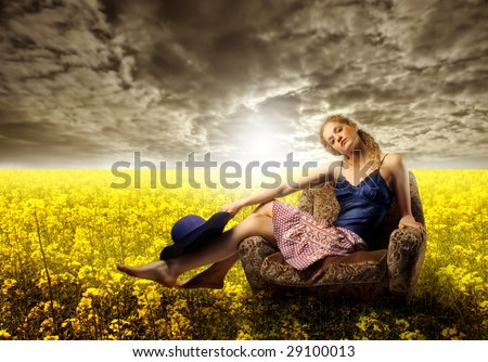 pretty girl sited on armchair in a field of yellow flowers - stock photo