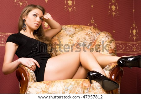 Pretty girl sits near an armchair.