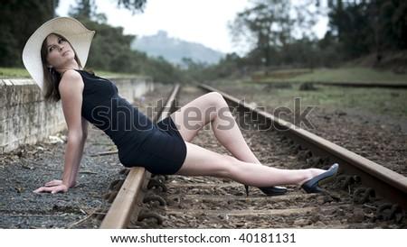 Pretty girl sits on railway - stock photo