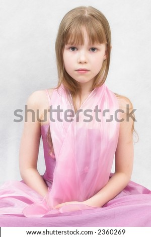 Pretty girl sits. She wears lilac dress and  pink tippet.