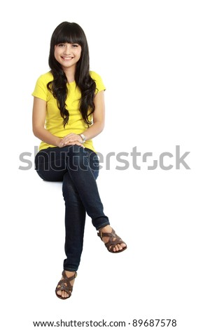 Pretty girl sitting casual on big blank billboard poster sign with lot of copy space - stock photo
