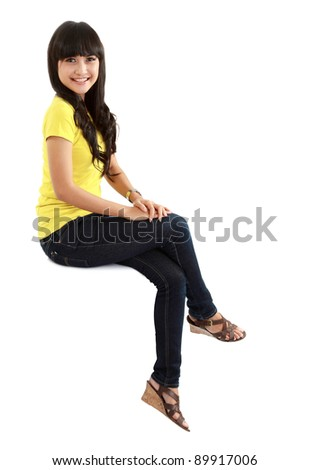 Pretty girl sitting casual on big blank billboard poster sign with lot of copy space.isolated on white background - stock photo