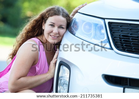 Pretty girl sitting her cheek against to the bumper of the car - stock photo