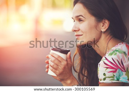 pretty girl sitting in street with morning coffee - stock photo