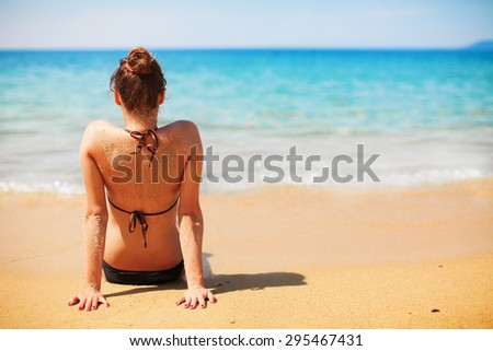 Pretty girl sitting on a beach in a bikini and enjoying in view of the open sea. - stock photo