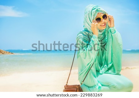 pretty girl sitting on a beach wearing traditional muslim costume - stock photo