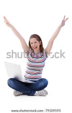 Pretty girl sitting on floor in tailor seat, shouting happily with upraised hands.? - stock photo