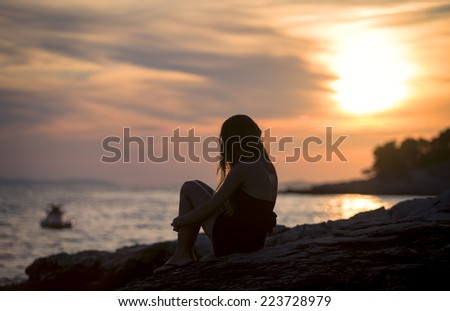 pretty girl sitting on seashore at sunset - stock photo