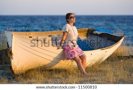 pretty girl sitting on the boat and looking to the sunset - stock photo