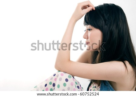 Pretty girl sitting on the floor,bending her arm,hand on head,contemplating - stock photo