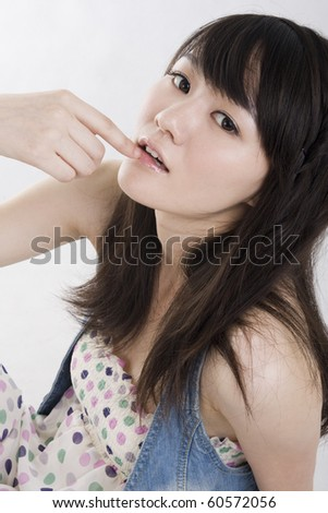 Pretty girl sitting on the floor,looking up,a finger on lips,contemplating - stock photo