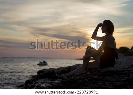 pretty girl sitting on the sea shore at sunset and looks into the distance - stock photo