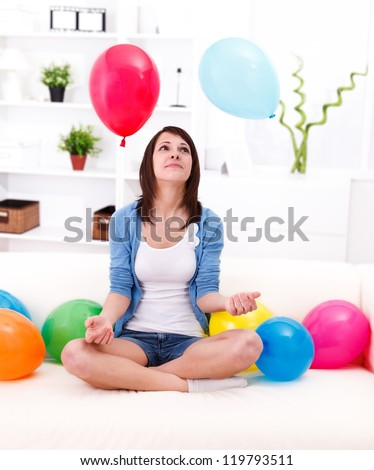 Pretty girl sitting on the sofa with plenty of balloons around