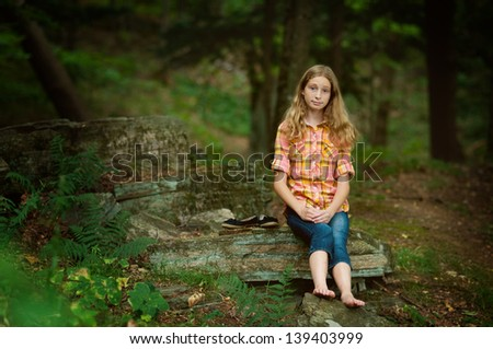 pretty girl sitting out on a rock in a forest during the summer - stock photo