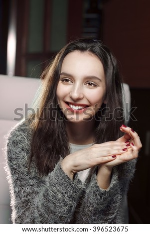 pretty girl sitting with hands near her chin, smiling and attentively listening to - stock photo